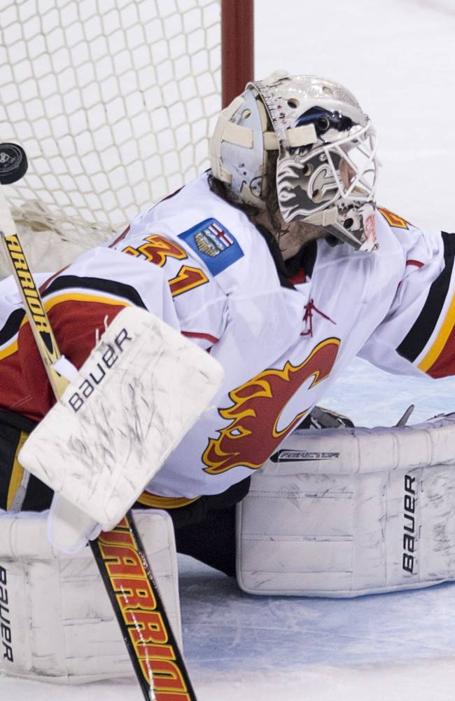 Vancouver Canucks' Yannick Weber's shot goes past Calgary Flames goalie Karri Ramo (31) during the third period of NHL action in Vancouver,  British Columbia Saturday Jan. 18, 2014