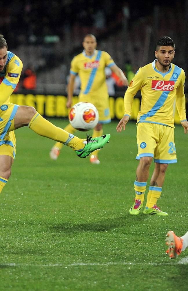 Napoli's Gonzalo Higuain, left, kicks the ball during an Europe League, round of 32, second leg, soccer match between Napoli and Swansea, at the Naples San Paolo stadium, Italy, Thursday, Feb. 27,  2014