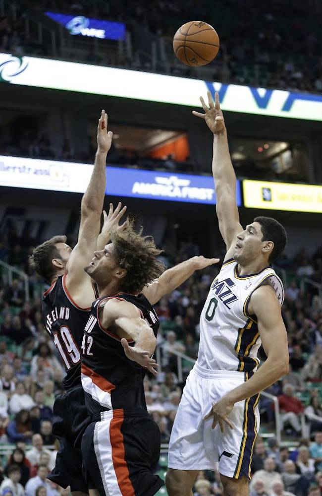 Utah Jazz's Enes Kanter (0) shoots as Portland Trail Blazers' Robin Lopez (42) and Joel Freeland (19) defend in the second half during an NBA preseason basketball game Wednesday, Oct. 16, 2013, in Salt Lake City. The Trail Blazers won 99-92