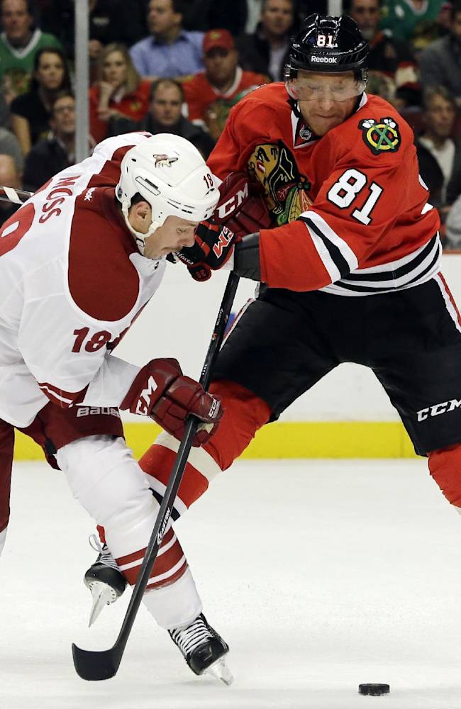 Phoenix Coyotes' David Moss, left, and Chicago Blackhawks' Marian Hossa battle for the puck during the first period of an NHL hockey game in Chicago, Thursday, Nov. 14, 2013