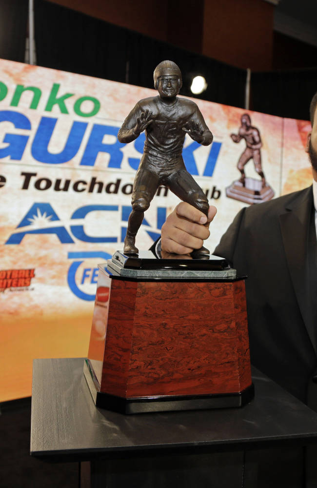 Pittsburgh's Aaron Donald poses for a photo with the Bronko Nagurski award for the NCAA college football defensive player of the year during a news conference in Charlotte, N.C., Monday, Dec. 9, 2013. Donald averaged 2.2 tackles for loss per game while ranking 10th in forced fumbles and 13th in sacks per game