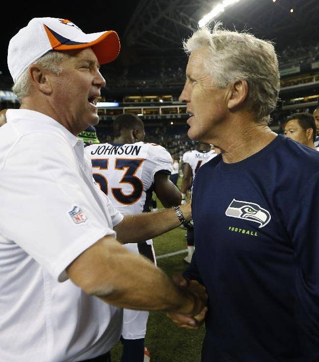 In this photo taken Aug. 17, 2013, Seattle Seahawks head coach Pete Carroll, right, shakes hands with Denver Broncos head coach John Fox, left, after the Seahawks beat the Broncos 40-10 in a preseason NFL football game in Seattle. The two teams square off in Super Bowl XLVIII on Sunday, Feb. 2, 2014, in East Rutherford, N.J