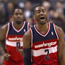 Washington Wizards' John Wall, right, reacts after Martell Webster, left, scores against the Toronto Raptors during the last minute of triple overtime in NBA basketball action in Toronto, Thursday, Feb. 27, 2014 The Associated Press