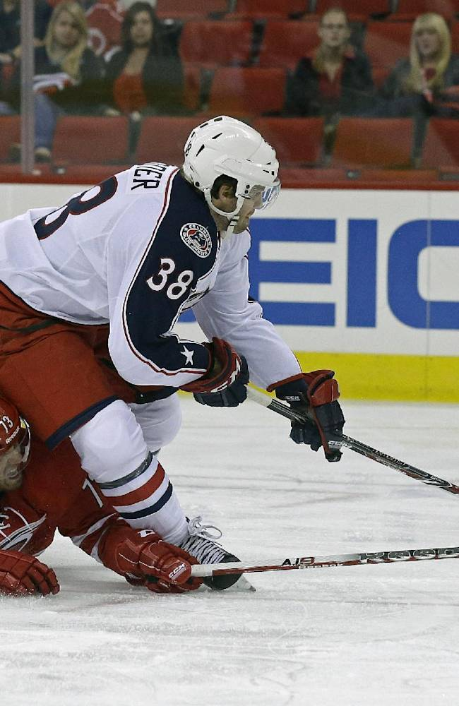 Carolina Hurricanes' Brett Bellemore (73) falls to the ice as he reaches for the puck against Columbus Blue Jackets' Boone Jenner (38) during the first period of an NHL preseason hockey game in Raleigh, N.C., Wednesday, Sept. 18, 2013