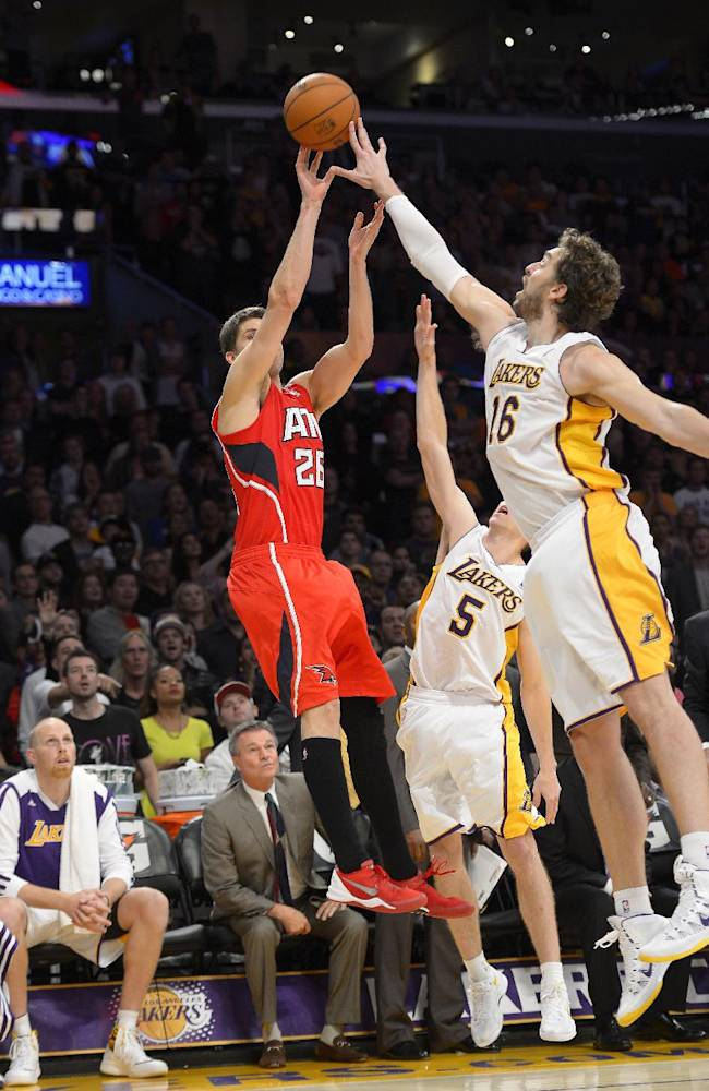Los Angeles Lakers forward Pau Gasol, right, of Spain, blocks a shot by Atlanta Hawks forward Kyle Korver in the last few second of their NBA basketball game, Sunday, Nov. 3, 2013, in Los Angeles. The Lakers won 105-103