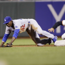 San Francisco Giants' Hunter Pence, right, is safe at second as Los Angeles Dodgers second baseman Dee Gordon, left, misses the throw to the base after a ground ball from Michael Morse during the sixth inning of a baseball game on Tuesday, April 15, 2014,