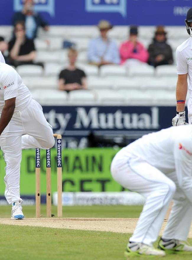 Sri Lanka's Rangana Herath, left, bowls to England's Moeen Ali  during day five of the Second Test Match between England and Sri Lanka at Headingley cricket ground, Leeds, England, on Tuesday, June 24, 2014