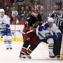 Phoenix Coyotes' Radim Vrbata (17), of the Czech Republic, checks Vancouver Canucks' Zack Kassian (9) into the boards as linesman Steve Miller (89) tries to get out of the way and Canucks' Dan Hamhuis (2) looks on during the first period of an NHL hockey