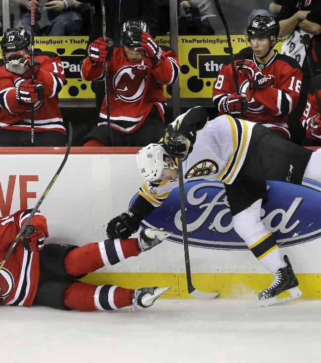 New Jersey Devils players react on the bench as Devils' Tuomo Ruutu, front left, of Finland, collides with Boston Bruins' Kevan Miller (86) during the third period of an NHL hockey game in Newark, N.J., Sunday, April 13, 2014. The Devils won 3-2