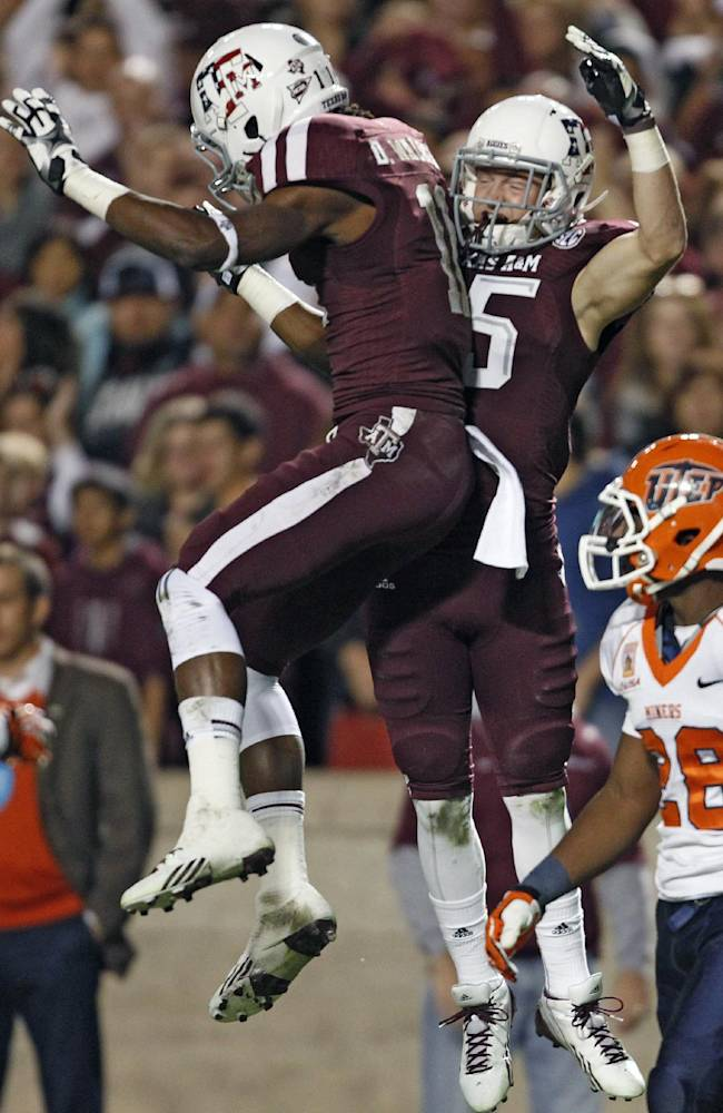 Texas A&M's Travis Labhart, center, celebrates his 44-yard touchdown reception with teammate Derel Walker as UTEP's Demaracus Kizzie looks on during the first half of an NCAA college football game, Saturday, Nov. 2, 2013 in College Station, Texas