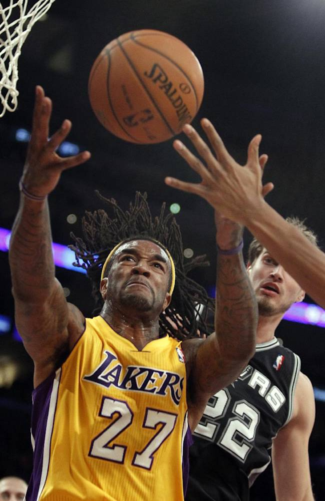 Los Angeles Lakers center Jordan Hill (27) pulls down a rebound in front of San Antonio Spurs center Tiago Splitter, right, of Brazil, during an NBA basketball game on Friday, Nov. 1, 2013, in Los Angeles. The Spurs won 91-85