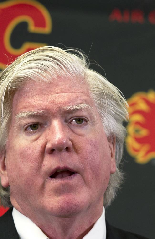 Brian Burke, Calgary Flames' president of hockey operations, announces the firing of general manager Jay Feaster and assistant general manager John Weisbrod during a NHL hockey news conference Thursday, Dec. 12, 2013, in Calgar, Alberta. Burke will serve as acting general manager