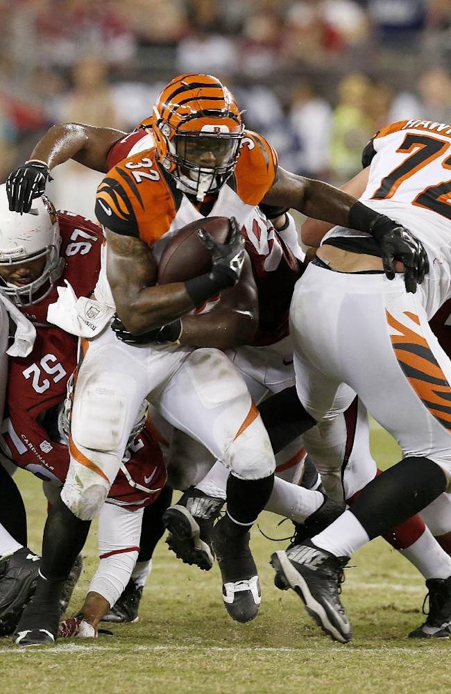 Cincinnati Bengals' Jeremy Hill (32) breaks through the line as he runs with the ball against the Arizona Cardinals during the second half of an NFL preseason football game Sunday, Aug. 24, 2014, in Glendale, Ariz.  The Bengals defeated the Cardinals 19-13