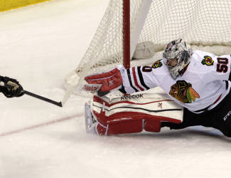 Chicago Blackhawks goalie Corey Crawford (50) blocks a shot by Colorado Avalanche left wing Alex Tanguay (40) during the first period of Chicago's 5-2 victory in an NHL hockey game in Denver, Saturday, Dec. 27, 2014. (AP Photo/Joe Mahoney)