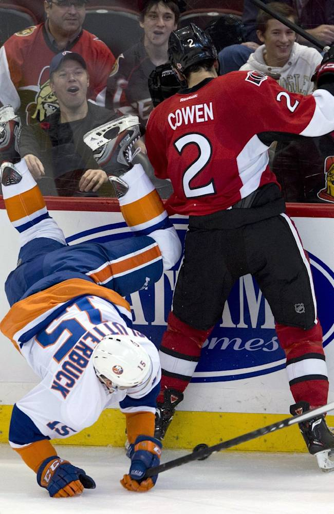 Ottawa Senators defenseman Jared Cowen gets the upper hand on New York Islanders right wing Cal Clutterbuck along the boards during the second period of an NHL hockey game Friday, Nov. 1, 2013, in Ottawa, Ontario