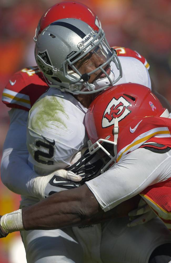 In this Oct. 13, 2013 file photo, Oakland Raiders quarterback Terrelle Pryor (2) is sacked by Kansas City Chiefs outside linebackers Justin Houston (50) and Tamba Hali (91) during the second half of an NFL football game at Arrowhead Stadium in Kansas City, Mo. Peyton Manning is taking a beating. His right ankle is a mess and the Broncos' offensive line is battered. And now here come the Kansas City Chiefs, leading the NFL in sacks. AP Photo/Reed Hoffmann, File)