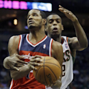 Washington Wizards' Trevor Ariza, left, is fouled by Milwaukee Bucks' Khris Middleton as he goes up for a shot during the first half of an NBA basketball game Wednesday, Nov. 27, 2013, in Milwaukee The Associated Press