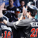 Miami Marlins' Christian Yelich returns to high-fives in the dugout after scoring on a single by teammate Casey McGehee during the first inning of a baseball game against the Philadelphia Phillies, Sunday, April 13, 2014, in Philadelphia The Associated Pr
