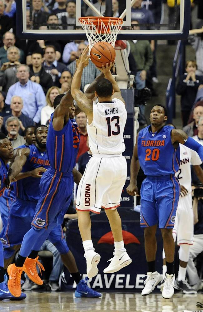 Connecticut's Shabazz Napier (13) goes up for the game winning basket at the buzzer during the second half of an NCAA college basketball game against Florida, Monday, Dec. 2, 2013, in Storrs, Conn. Connecticut won 65-64