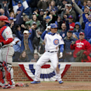 Chicago Cubs' Darwin Barney (15) reacts after sliding safely into home, next to Philadelphia Phillies catcher Carlos Ruiz during a baseball game Friday, April 4, 2014, in Chicago The Associated Press