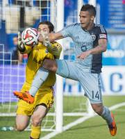 Sporting Kansas City's Dom Dwyer, right, goes in on Montreal Impact goalkeeper Troy Perkins during the second half of an MLS soccer game in Montreal, Saturday, May 10, 2014. (AP Photo/The Canadian Press, Graham Hughes)