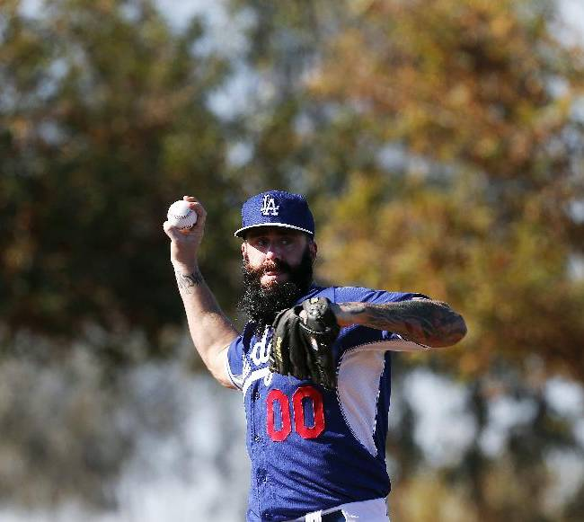 Los Angeles Dodgers' Brian Wilson works on pick off moves during spring training baseball practice Sunday, Feb. 9, 2014, in Glendale, Ariz