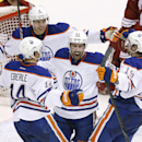 Edmonton Oilers' Sam Gagner (89) celebrates his goal against the Phoenix Coyotes with teammates Jordan Eberle (14), Taylor Hall (4) and Justin Schultz (19) during the third period of an NHL hockey game, Friday, April 4, 2014, in Glendale, Ariz. The Oiler