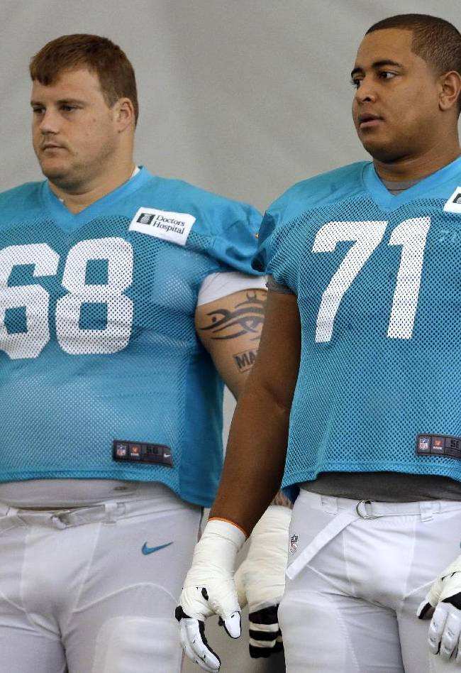 In this July 24, 2013, file photo, Miami Dolphins guard Richie Incognito (68) and tackle Jonathan Martin (71) stand on the field during NFL football practice in Davie, Fla. Incognito has lashed out at Martin on Twitter, saying