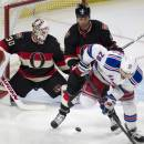 New York Rangers left wing Chris Kreider (20) tries to deflect the puck past Ottawa Senators goalie Andrew Hammond, left, under pressure from defenseman Marc Methot during the second period of an NHL hockey game Thursday, March 26, 2015, in Ottawa, Ontario. (AP Photo/The Canadian Press, Adrian Wyld)