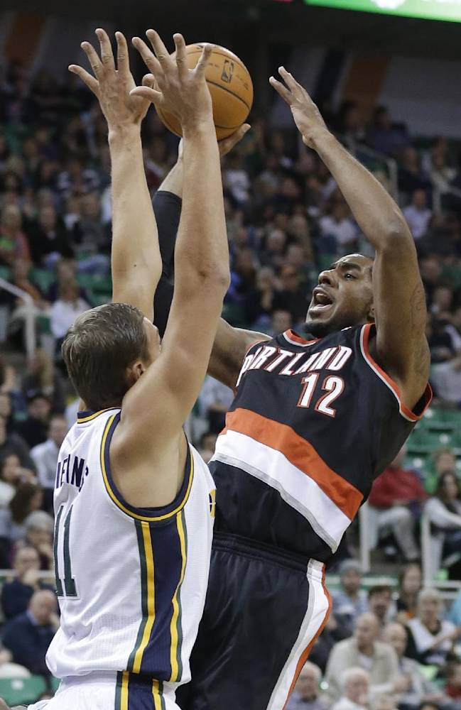 Portland Trail Blazers' LaMarcus Aldridge (12) shoots as Utah Jazz's Andris Biedrins (11) defends in the first half during an NBA preseason basketball game Wednesday, Oct. 16, 2013, in Salt Lake City