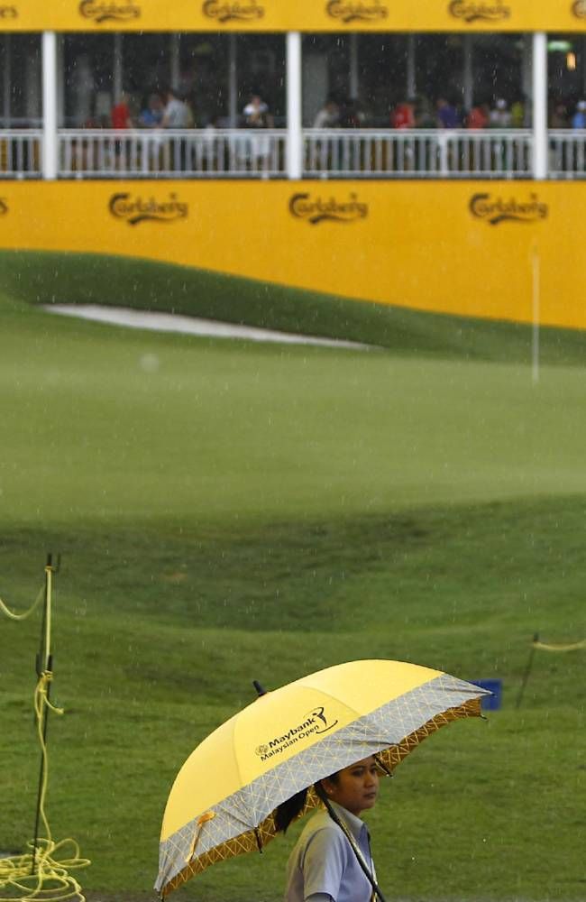 A tournament staff member holding an umbrella walks past the eighteenth green in the rain during the final round of the Malaysian Open golf tournament at Kuala Lumpur Golf and Country Club in Kuala Lumpur, Malaysia, Sunday, April 20, 2014. The play was suspended due to heavy rain