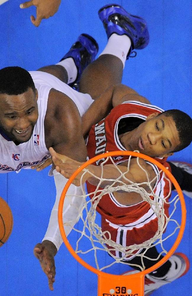 Los Angeles Clippers forward Glen Davis, left, puts up a shot as Milwaukee Bucks guard Giannis Antetokounmpo, of Greece, defends during the first half of an NBA basketball game, Monday, March 24, 2014, in Los Angeles