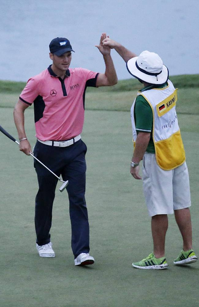 Martin Kaymer of Germany congratulates caddie Craig Connelly after making par on the 17th hole during the final round of The Players championship golf tournament at TPC Sawgrass, Sunday, May 11, 2014 in Ponte Vedra Beach, Fla. Kaymer won the championship