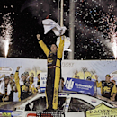 A happy Brendan Gaughan celebrates standing on his car in victory lane following his win in the NASCAR Nationwide auto race in Sparta, Ky., Saturday, Sept. 20, 2014. (AP Photo/Garry Jones)