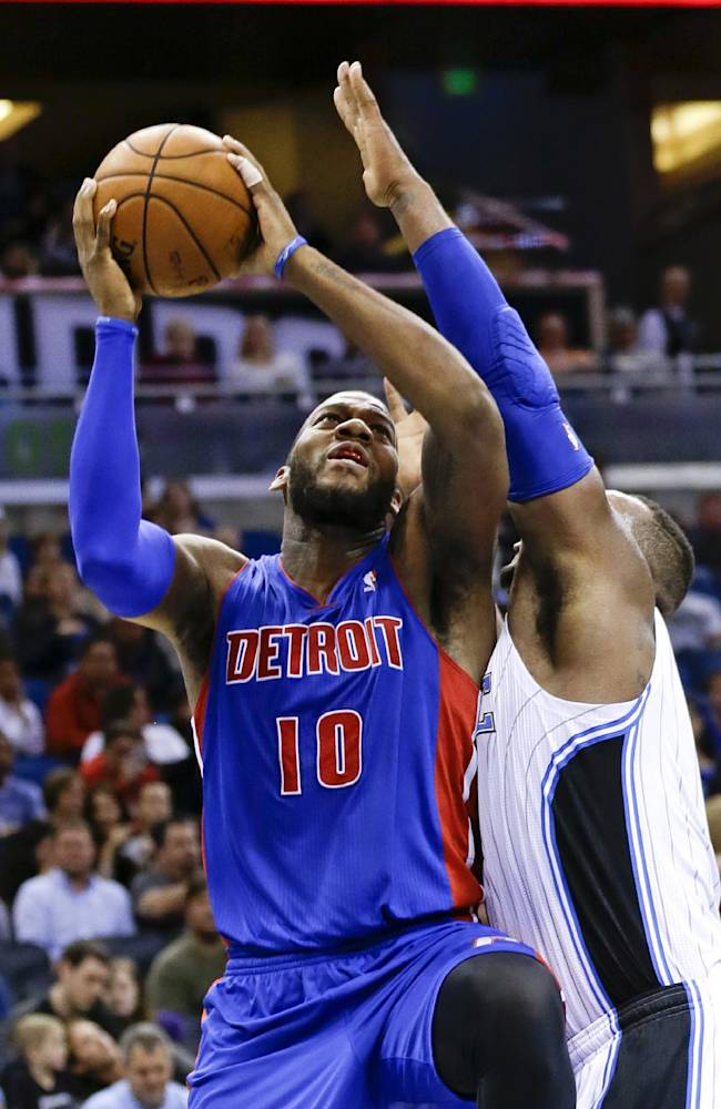 Detroit Pistons' Greg Monroe (10) shoots as he gets around Orlando Magic's Glen Davis, right, during the first half of an NBA basketball game in Orlando, Fla., Friday, Dec. 27, 2013