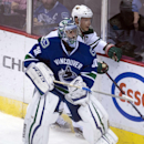 Minnesota Wild center Mikko Koivu (9) tries to squeeze past Vancouver Canucks goalie Ryan Miller (30) during the first period of NHL action in Vancouver, British Columbia, Canada, Sunday, Feb. 1, 2015 The Associated Press