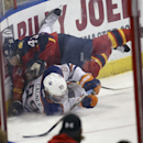 Florida Panthers' Mike Weaver (43) and Edmonton Oilers' Sam Gagner (89) slide into the wall, while chasing the puck, during the second period of an NHL hockey game in Sunrise, Fla., Tuesday, Nov. 5, 2013. (AP J Pat Carter) The Associated Press