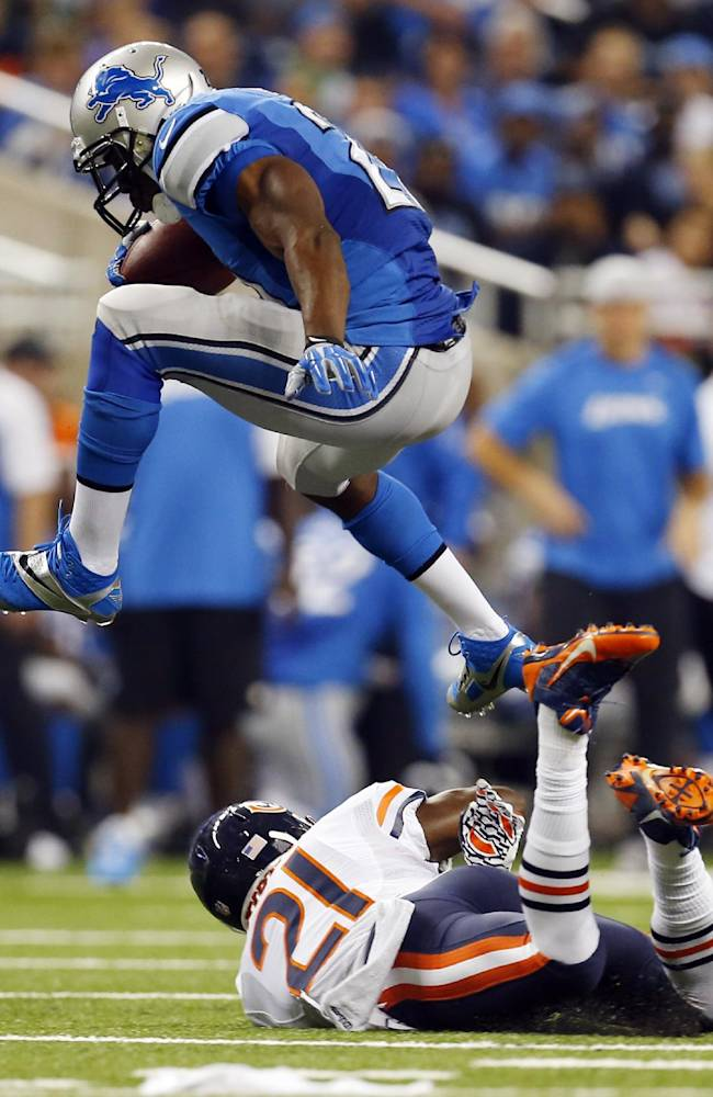 Detroit Lions running back Reggie Bush, top, jumps over Chicago Bears strong safety Major Wright (21) while heading for the end zone on a 37-yard touchdown run during the second quarter of an NFL football game at Ford Field in Detroit, Sunday, Sept. 29, 2013