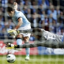 FILE - Manchester City's Carlos Tevez, left, attempts to shoot past Wigan Athletic goalkeeper Joel Robles during their English FA Cup final soccer match at Wembley Stadium, London, in this Saturday, May 11, 2013 file photo. Tevez was reported late Tuesday June 25 2013 to have finalized a transfer to Juventus. (AP Photo/Matt Dunham, File)