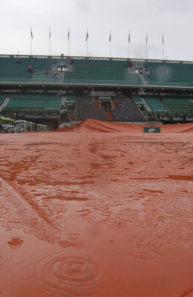 Rain drops splash on the canvas covering center court at the French Open tennis tournament ,Roland Garros stadium, in Paris, France, Wednesday, June 4, 2014. Rain delayed the start of the quarterfinal matches