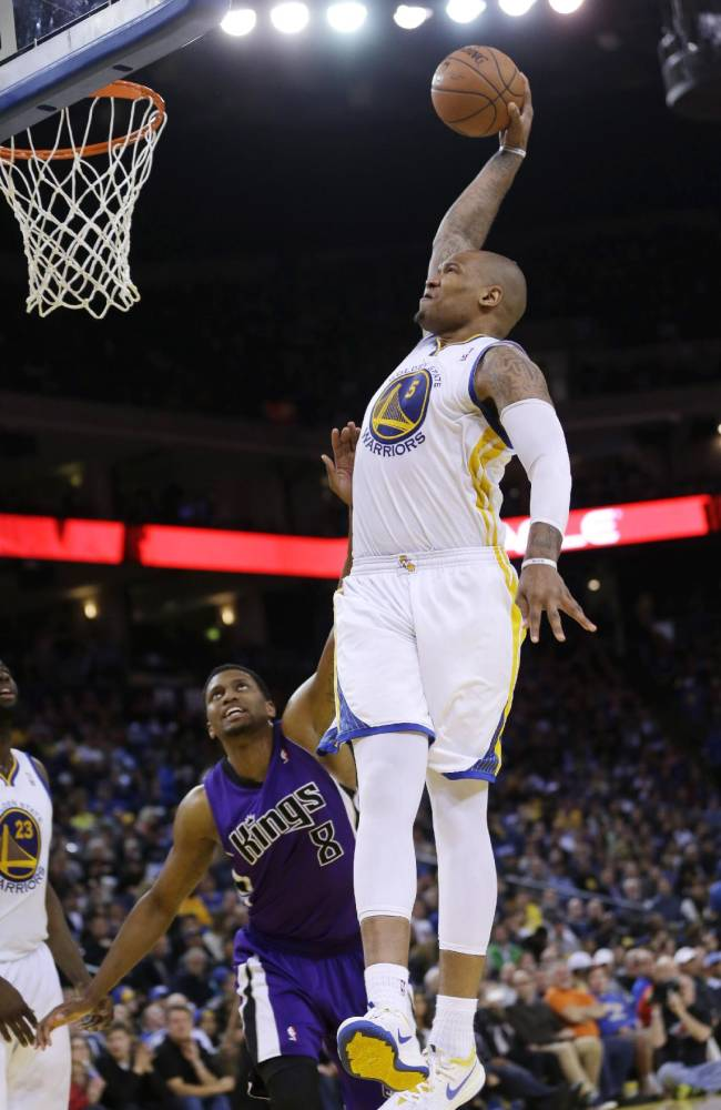 Golden State Warriors forward Marreese Speights goes up for a dunk next to Sacramento Kings forward Rudy Gay (8) during the second half of an NBA basketball game  Friday, April 4, 2014, in Oakland, Calif