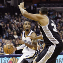 Memphis Grizzlies' Mike Conley (11) dribbles the ball past San Antonio Spurs' Boris Diaw, of France, in the first half of an NBA basketball game in Memphis, Tenn., Friday, Nov. 22, 2013 The Associated Press