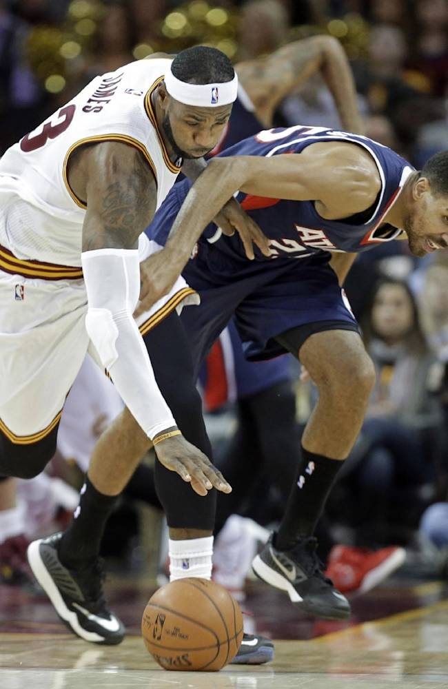 Cleveland Cavaliers' LeBron James, left, and Atlanta Hawks' Thabo Sefolosha, from Switzerland, chase down a loose ball in the first quarter of an NBA basketball game Wednesday, Dec. 17, 2014, in Cleveland. (AP Photo/Mark Duncan)