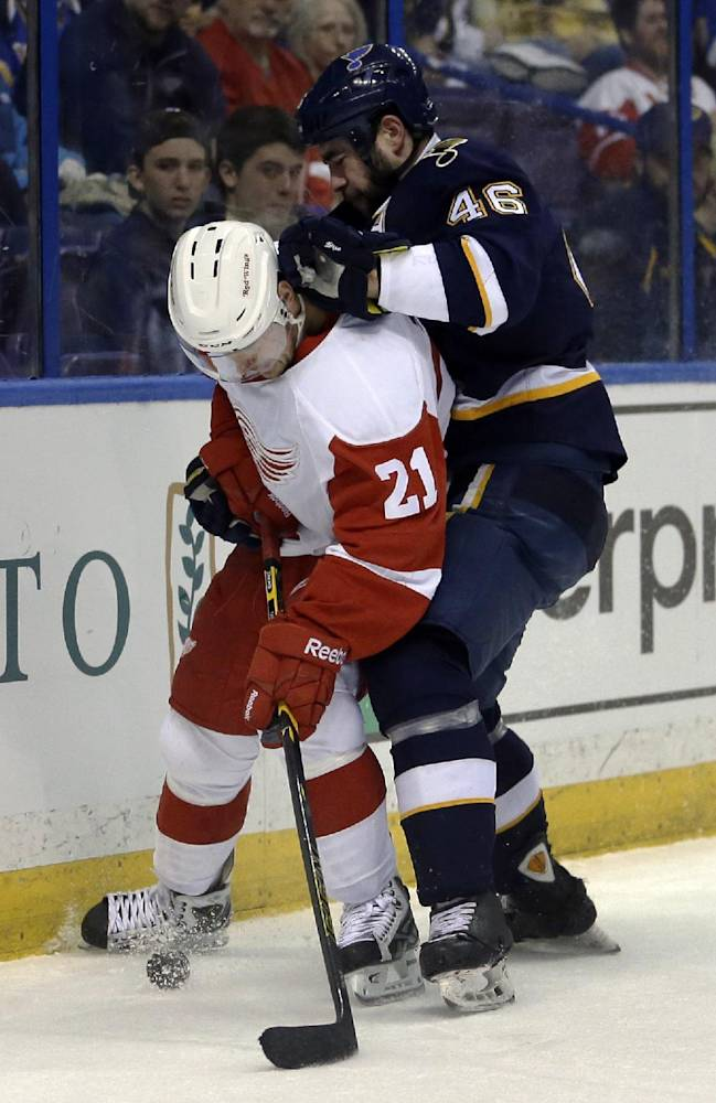 Detroit Red Wings' Tomas Tatar, left, of Slovakia, and St. Louis Blues' Roman Polak, of the Czech Republic, vie for a loose puck during the first period of an NHL hockey game Sunday, April 13, 2014, in St. Louis