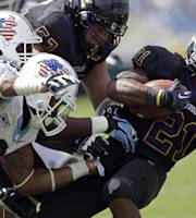 North Carolina's Travis Hughes (9) and Justin Thomason move in to tackle East Carolina's Vintavious Cooper (21) during the first half of an NCAA college football game in Chapel Hill, N.C., Saturday, Sept. 28, 2013. (AP Photo/Gerry Broome)