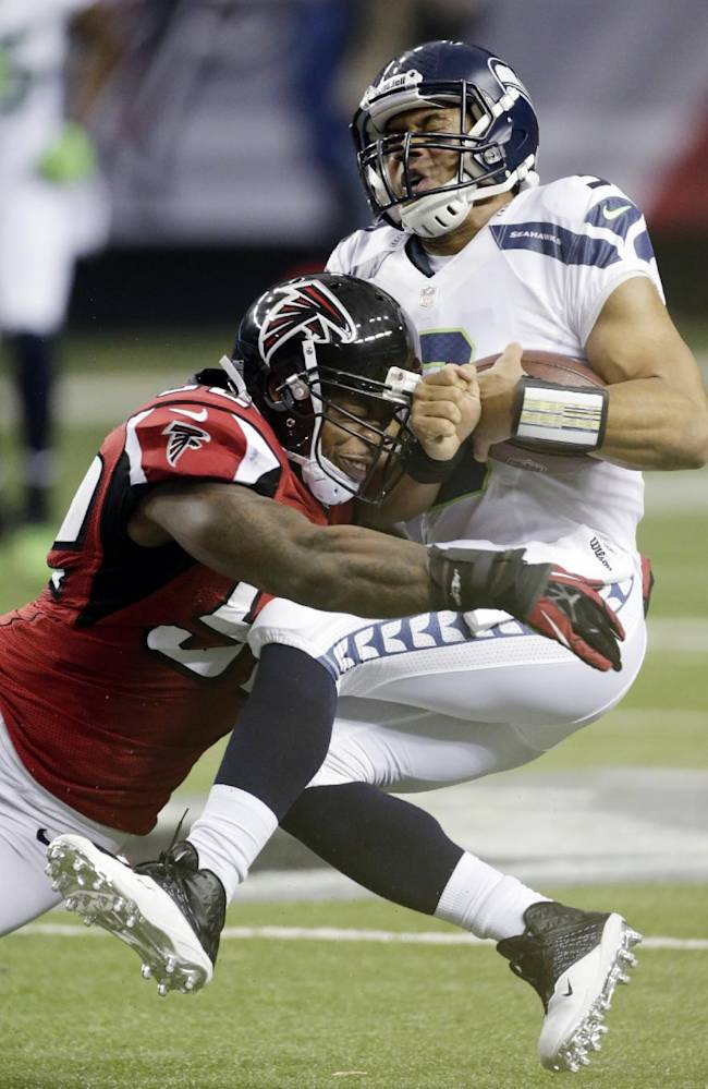 In this jan. 13, 2013 file photo, Seattle Seahawks quarterback Russell Wilson (3) is sacked by Atlanta Falcons middle linebacker Akeem Dent (52) during the first half of an NFC divisional playoff NFL football game, in Atlanta. The NFC divisional playoff game in Atlanta last January was nearly a crowning moment for Wilson and the Seahawks, overcoming a 20-point deficit to take a late lead. It all disappeared in the final 31 seconds and even 10 months later remains a sore spot that gets highlighted this week with the Seahawks headed back to Atlanta