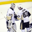 Pittsburgh Penguins center Sidney Crosby (87) celebrates with goalie Jeff Zatkoff (37) after they beat the Washington Capitals 3-2 in an NHL hockey game, Monday, March 10, 2014, in Washington. (AP Photo/Nick Wass)