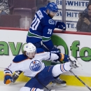 Vancouver Canucks left wing Chris Higgins (20) fights for control of the puck with Edmonton Oilers defenceman Jeff Petry (2) during the second period of NHL action in Vancouver, British Columbia Saturday, Oct. 11, 2014 The Associated Press