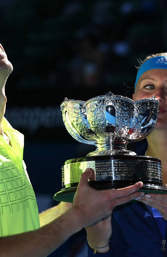 Kristina Mladenovic of France and Daniel Nestor of Canada hold the trophy after defeating Sania Mirza of India and Horia Tecau of Romania in their mixed doubles final at the Australian Open tennis championship in Melbourne, Australia, Sunday, Jan. 26, 2014