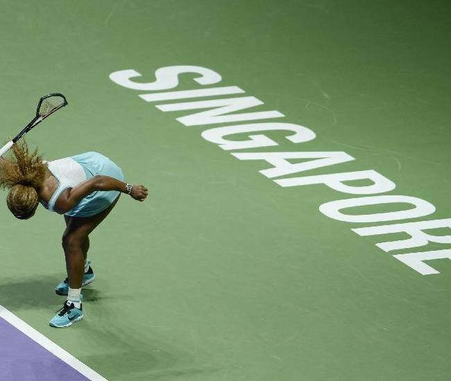 In this photo released by the World Sport Group, Serena Williams of the U.S. smashes her racket in frustration during her semifinal match against Denmark's Caroline Wozniacki at the WTA tennis finals in Singapore, Saturday, Oct. 25, 2014